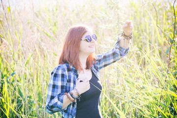 Happy beautiful young woman on summer meadow in tall grass