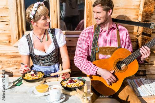 Leinwanddruck Bild Paar auf Berghütte musiziert isst Kaiserschmarrn