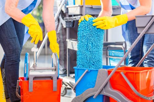 Leinwanddruck Bild Raumpflegerinnen bei Arbeit reinigen Boden