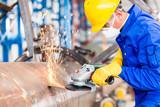 Metal worker in factory grinding metal of pipeline - 77625442