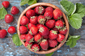 Ripe strawberries in wooden bowl and green leaves on old table,