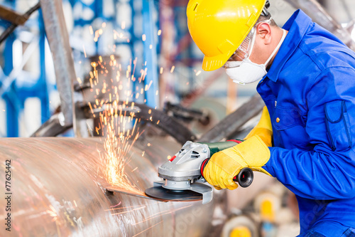 Metal worker in factory grinding metal of pipeline - 77625442
