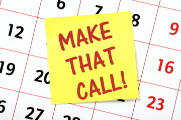 Make That Call reminder note posted on a wall calendar
