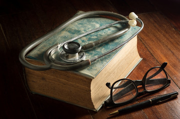 Stethoscope with eyeglasses,pen and antique book.