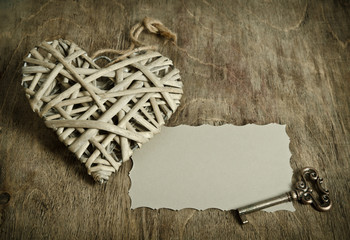 wicker heart handmade with the key lying on a wooden base with a