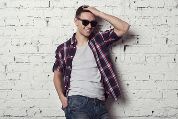 Young handsome attractive man hipster with sunglasses his hand