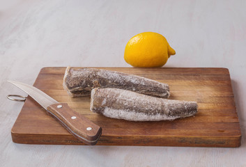 Two frozen carcass of hake and lemon on the cutting board