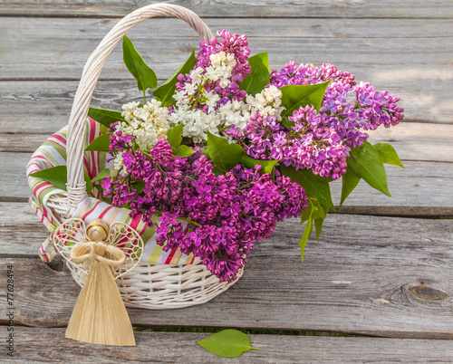 Foto op Canvas Lilac Bouquet of lilac and straw angel on a wooden table