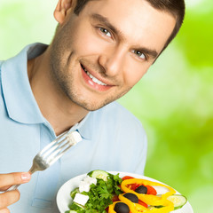 Young happy man eating salad, outdoor