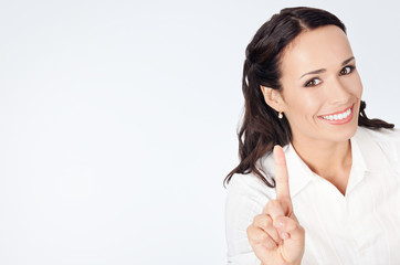Businesswoman showing one finger, on grey