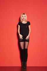 blonde lady in black posing on red