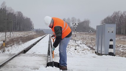 Worker clean the rails with a snow shovel