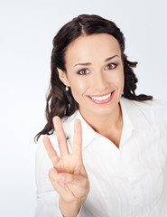Businesswoman showing three fingers, on grey