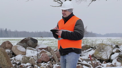 Worker with tablet PC near at the piles of stones