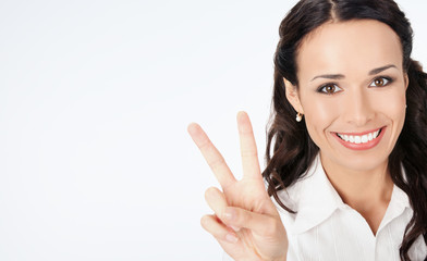 Businesswoman showing four fingers, on grey
