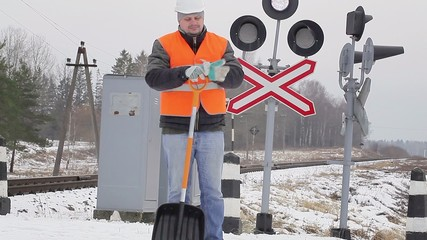 Man with cell phone and snow shovel on a railway crossing