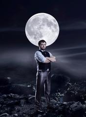 Businessman in the night agaist a big moon