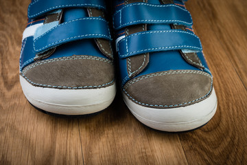 blue sneakers on wooden background
