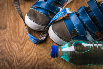 Pair of sport shoes and water bottle on wooden background