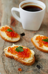 Canape with red caviar and cup of coffee
