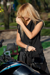 Blonde with long hair near motorcycle