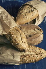 Variety of breads with seeds and nuts, on blue grunge background