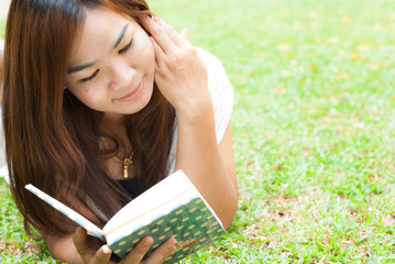 beautiful asian woman reading a book in the garden