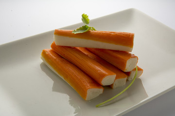 Surimi or crab sticks in a white rectangular plate. . White back