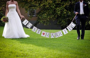 brautpaar mit just married banner