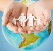 human hands holding paper family over earth globe