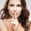Woman with finger on lips, on grey