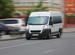 minibus goes on the city street - 77636884