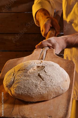 Tuinposter Brood Sacando el pan del horno.Horneando pan.