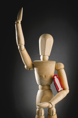Wooden man holding book.