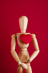 Wooden model with red heart on his chest.