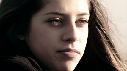 sad female teenager on the beach in winter closeup