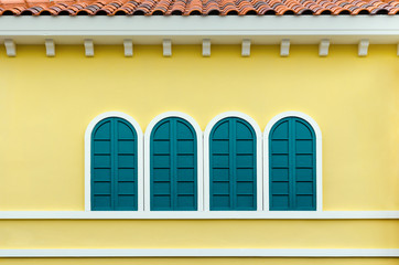 Four green arched windows on yellow wall