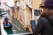 Young girl using a tablet to take pictures of gondolas of Venice