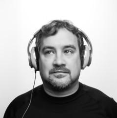 Caucasian Man wearing black shirt listening to DJ Style Headphon