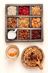granola muesli, nuts, honey, dried berries and milk. Top view.