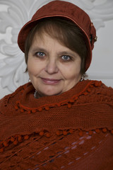 Mature woman in winter hat and knitted orange scarf