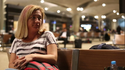 middle age bored blonde women waiting in airport
