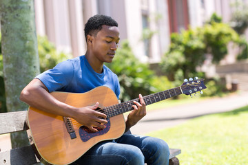 young african college student playing guitar