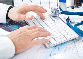 Male doctor writing on keyboard