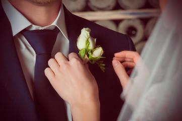 Невеста поправлят жениху бутоньерку на пиджаке