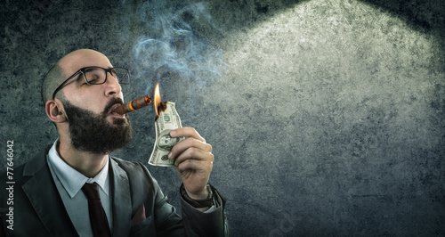 money burning - businessman arrogant - 77646042