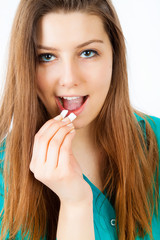 Young charming smiling woman puts in mouth chewing gum, close up