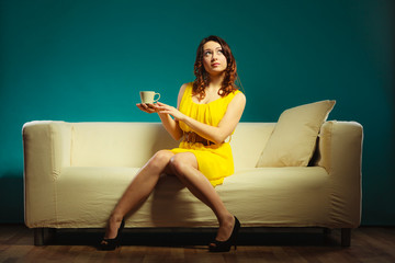 girl holds tea cup sitting on sofa