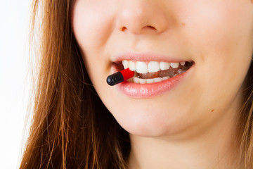 Young woman taking dark red pill. Isolated on white. Closeup.