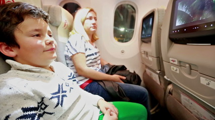 little child and mother watching movie in aircraft cabin